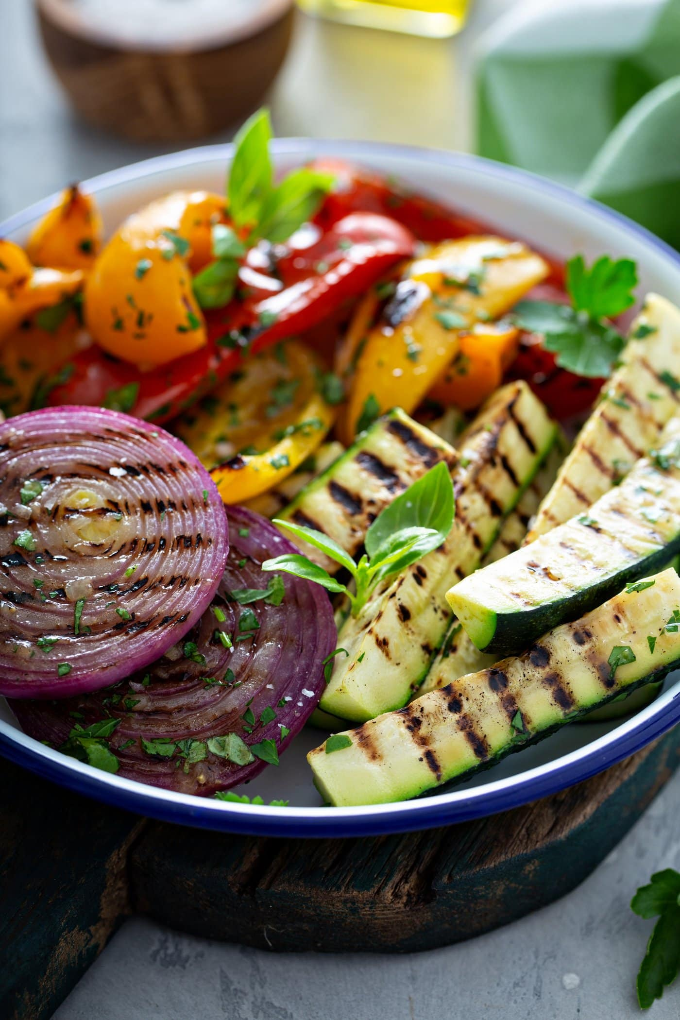 A serving dish of grilled veggies. The zucchini wedges, sliced red onions, and red and yellow bell peppers have perfect grill marks. and the veggies have a few parsley leaves scattered on top.