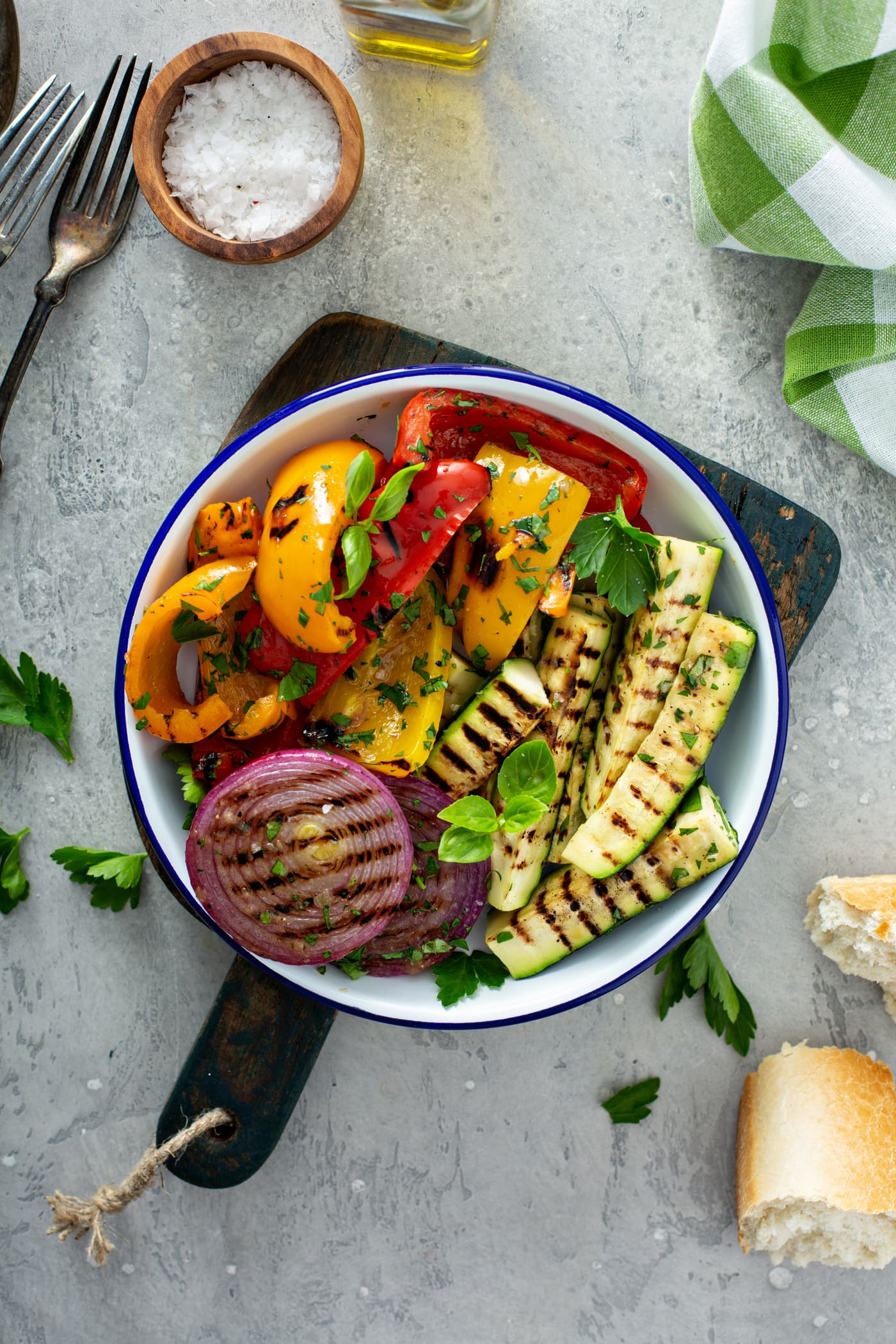 A serving plate of grilled vegetables sitting on a wooden cutting board. The grilled red onion, red and yellow bell peppers, and zucchini are topped with parsley leaves. A few parsley leaves are scattered on the table