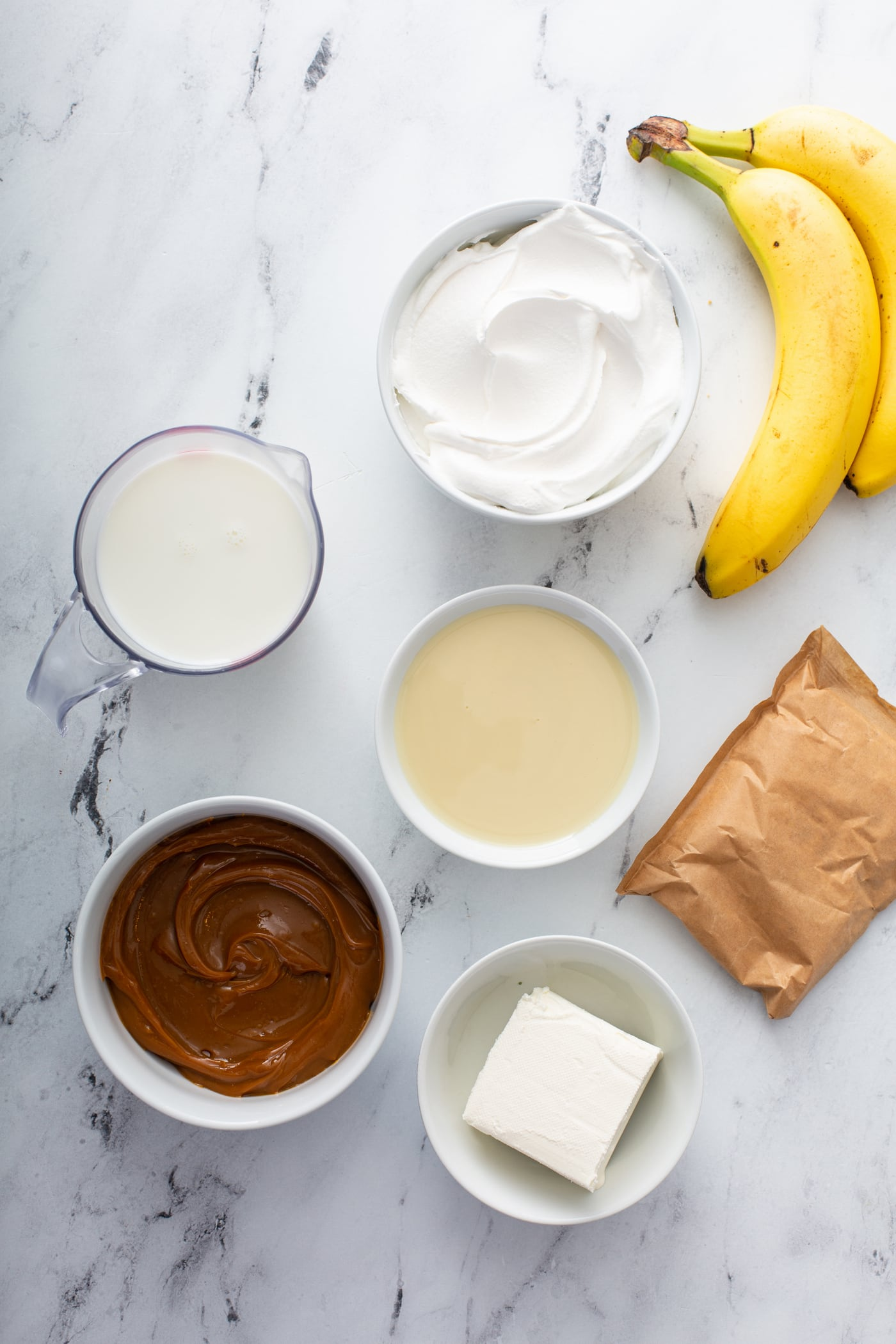 Ingredients for dulce de leche banana cream pie.  There are containers of dulce de leche, pudding, milk, cream, sugar, cream cheese and bananas.