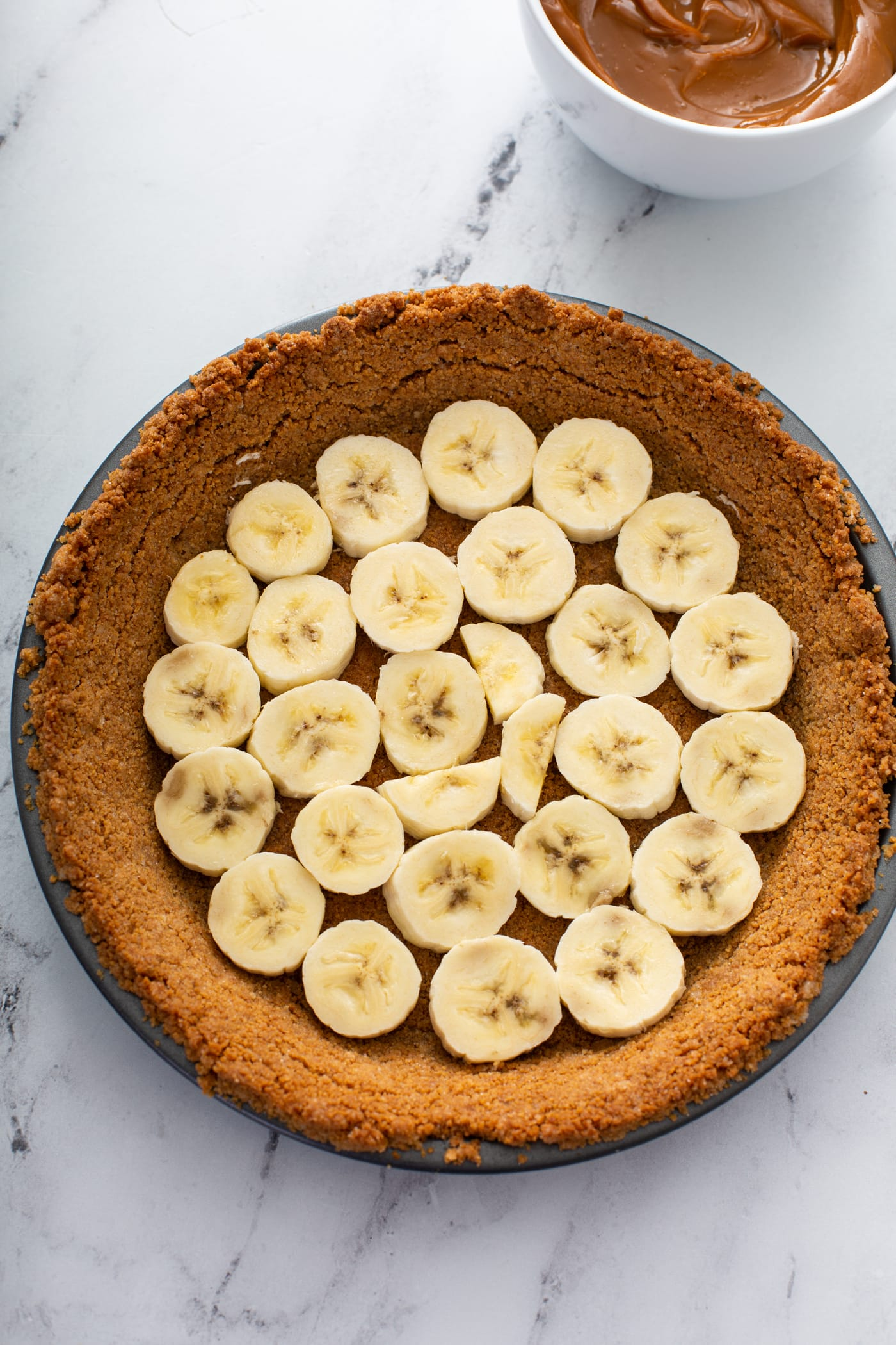A graham cracker crust with sliced bananas covering the bottom of the crust.