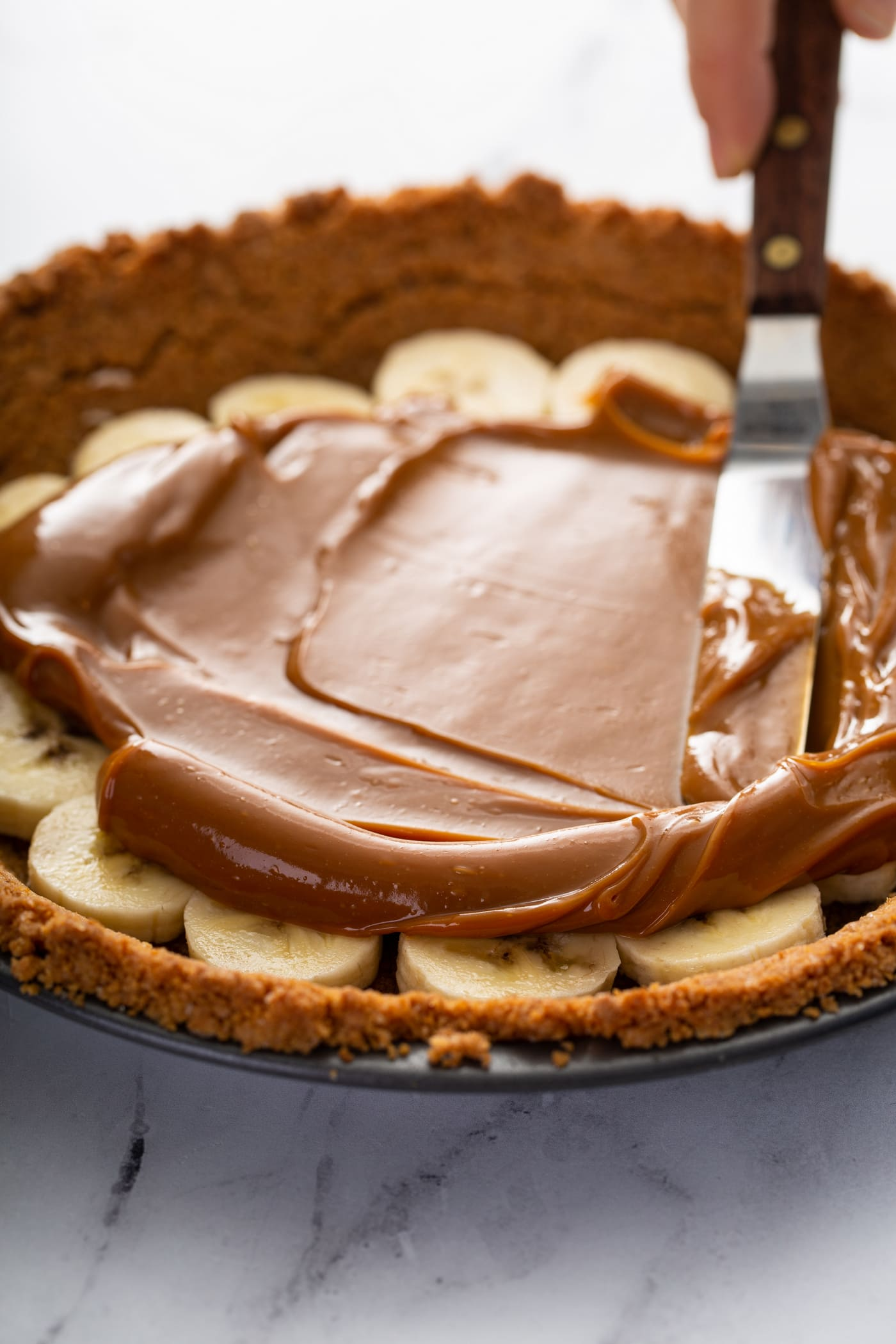 A graham cracker crust in a pie dish.  There are sliced bananas in the bottom of the crust and dulce de leche is being spread over the top of the bananas.