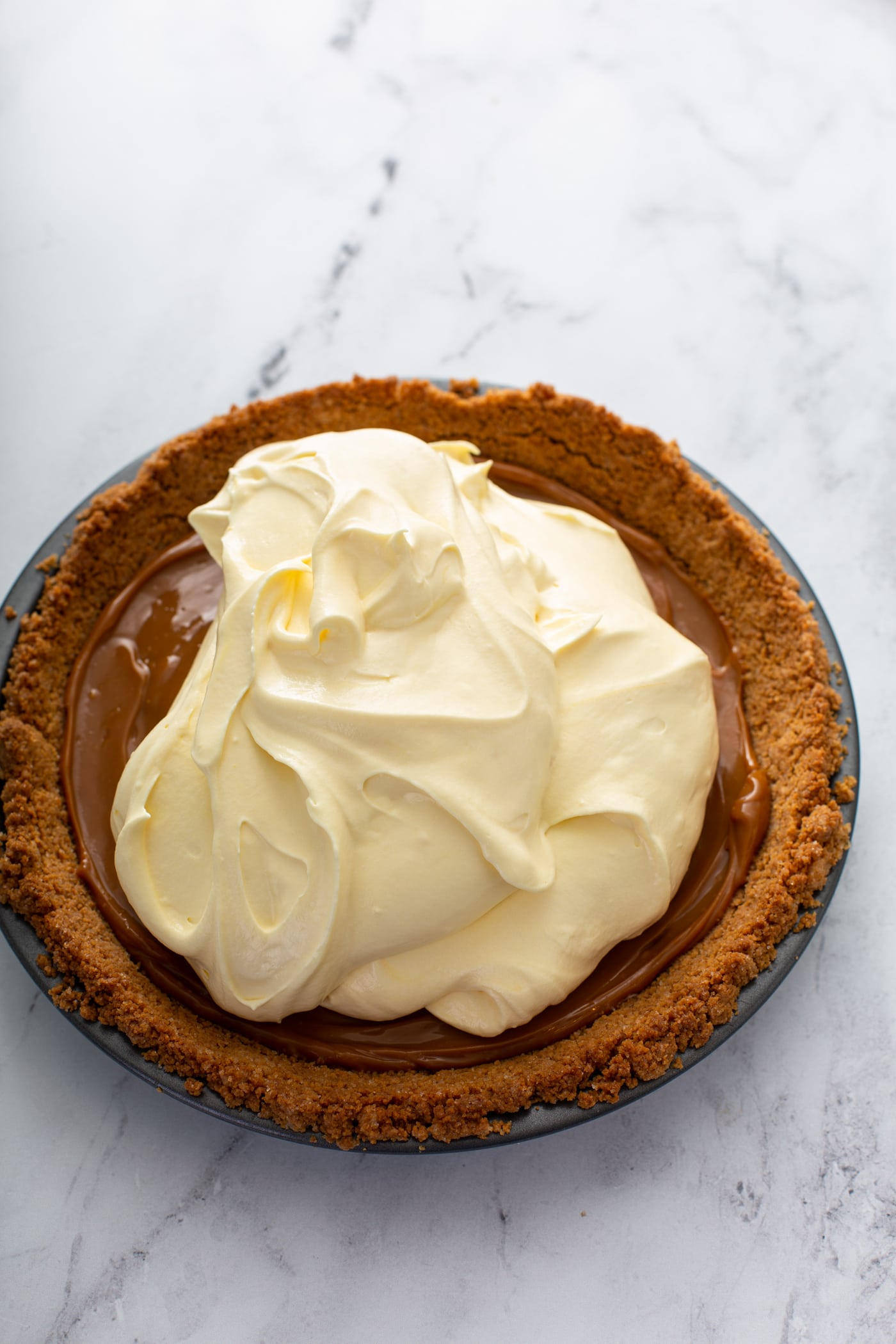 A graham cracker crust filled with dulce de leche and banana cream filling that has been added, but not yet spread all over the dulce de leche.