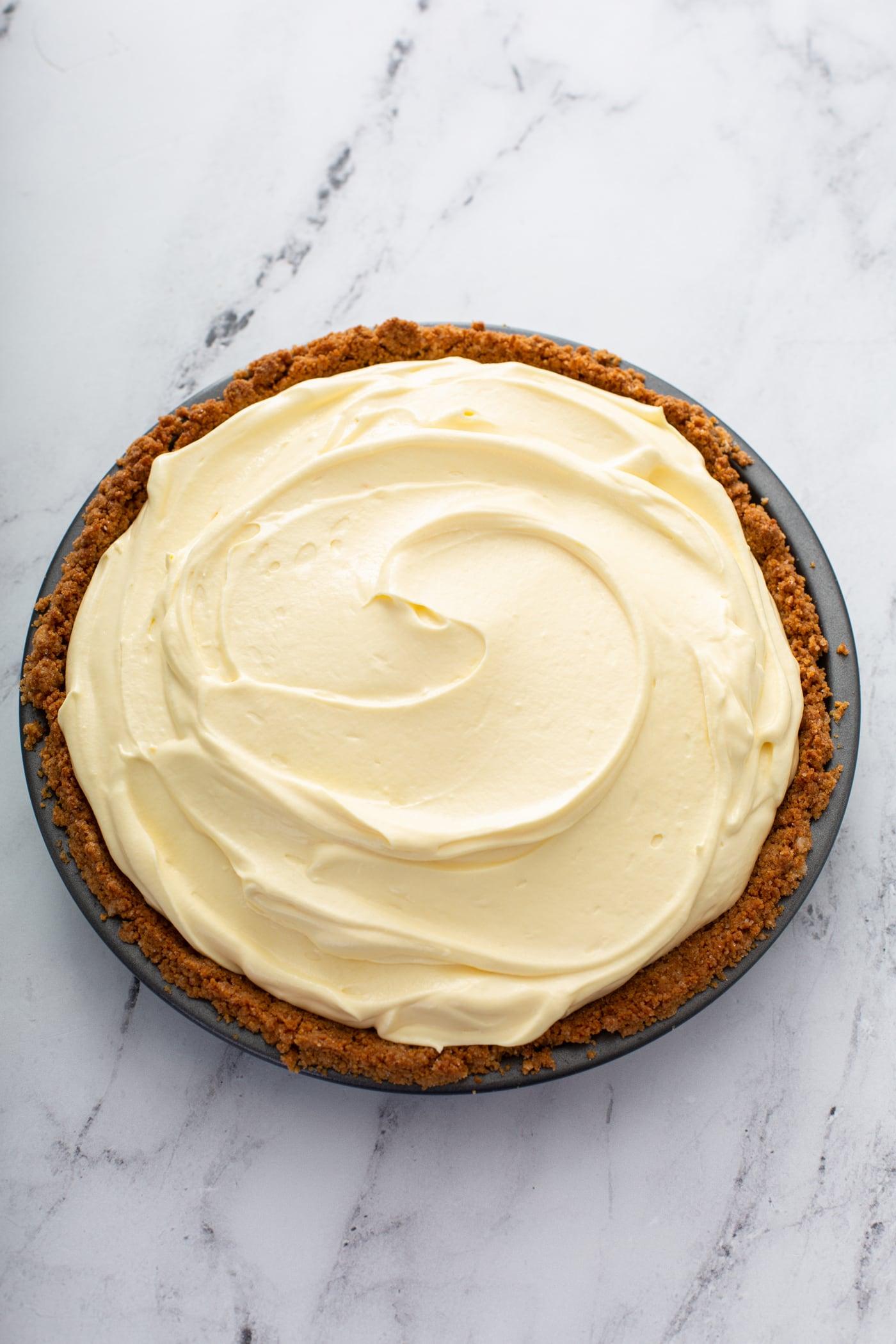 A dulce de leche banana cream pie in a graham cracker crust.  The filling is light yellow and the crust is a deep graham cracker brown.