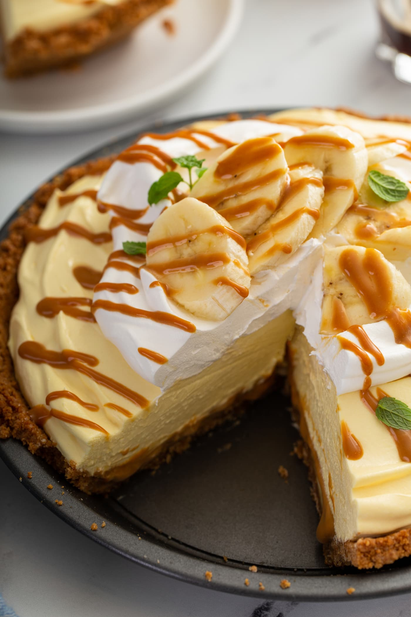A dulce de leche banana cream pie with whipped cream and sliced bananas on top.  The whole pie is drizzled with dulce de leche and a slice has been cut from the pie.