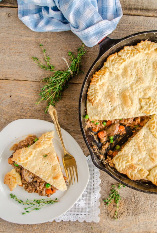 A 30 Minute Skillet Beef Pot Pie is shown with a slice removed and sitting on a plate next to the skillet.