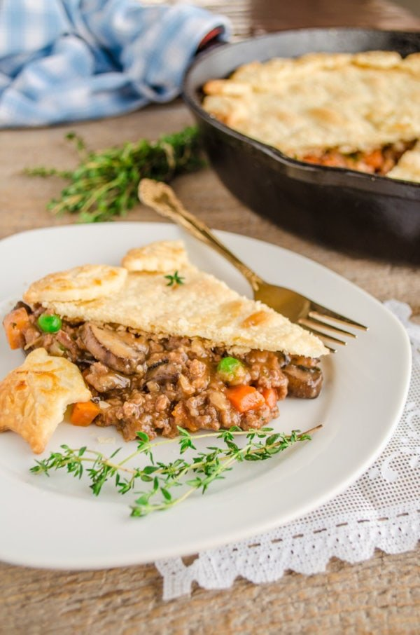 A slice of 30 Minute Skillet Beef Pot Pie sits on a plate garnished with fresh thyme.