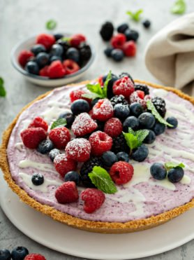 A whole white chocolate berry pie. The pie is topped with whole strawberries, raspberries, blue berries, blackberries, and mint leaves. There is a bowl of mixed berries in the background, and berries and a napkin on the table.