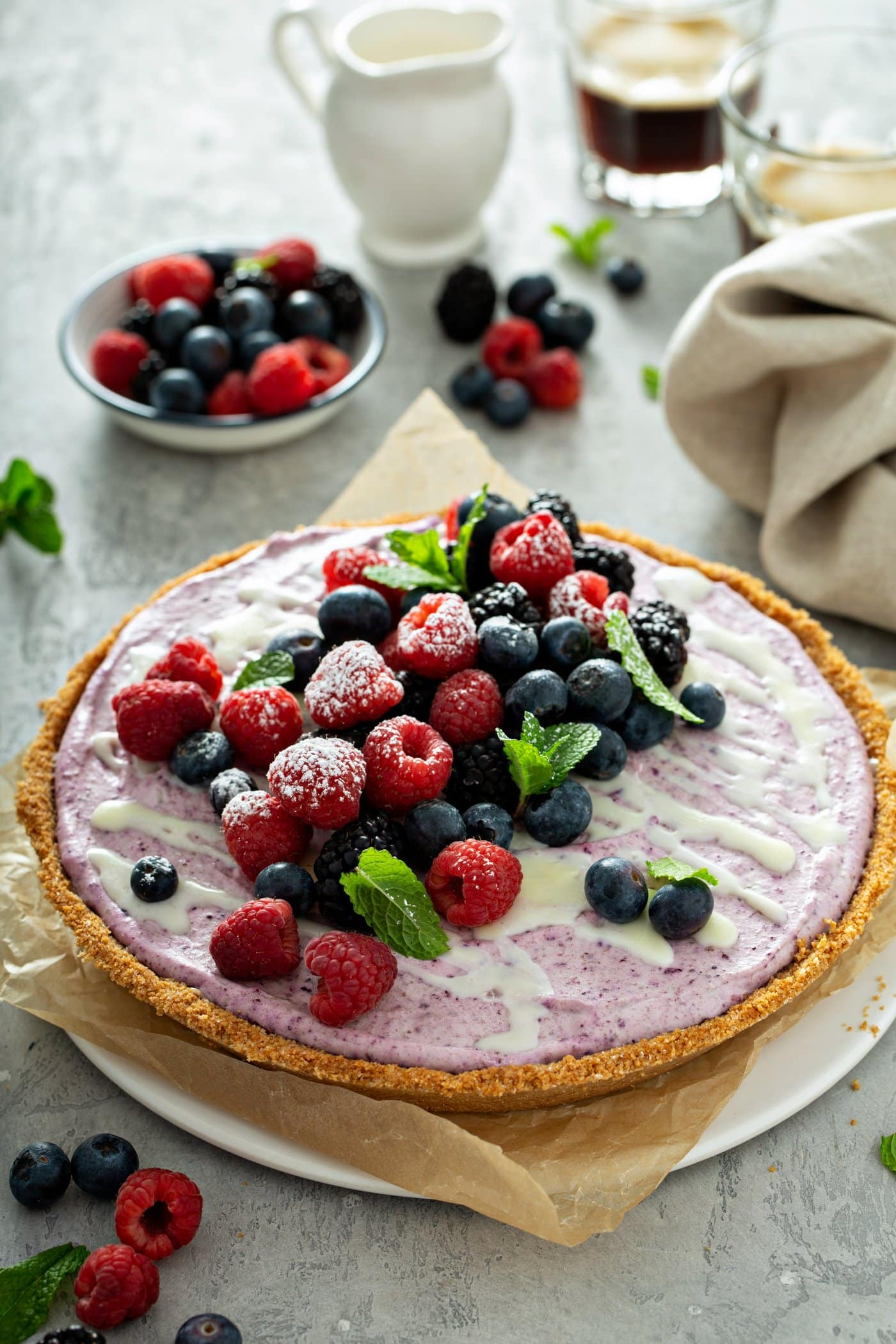 A whole white chocolate berry pie with mixed berries and mint leaves on top. A bowl of mixed berries is in the background and there are berries, mint leaves and a napkin on the table.