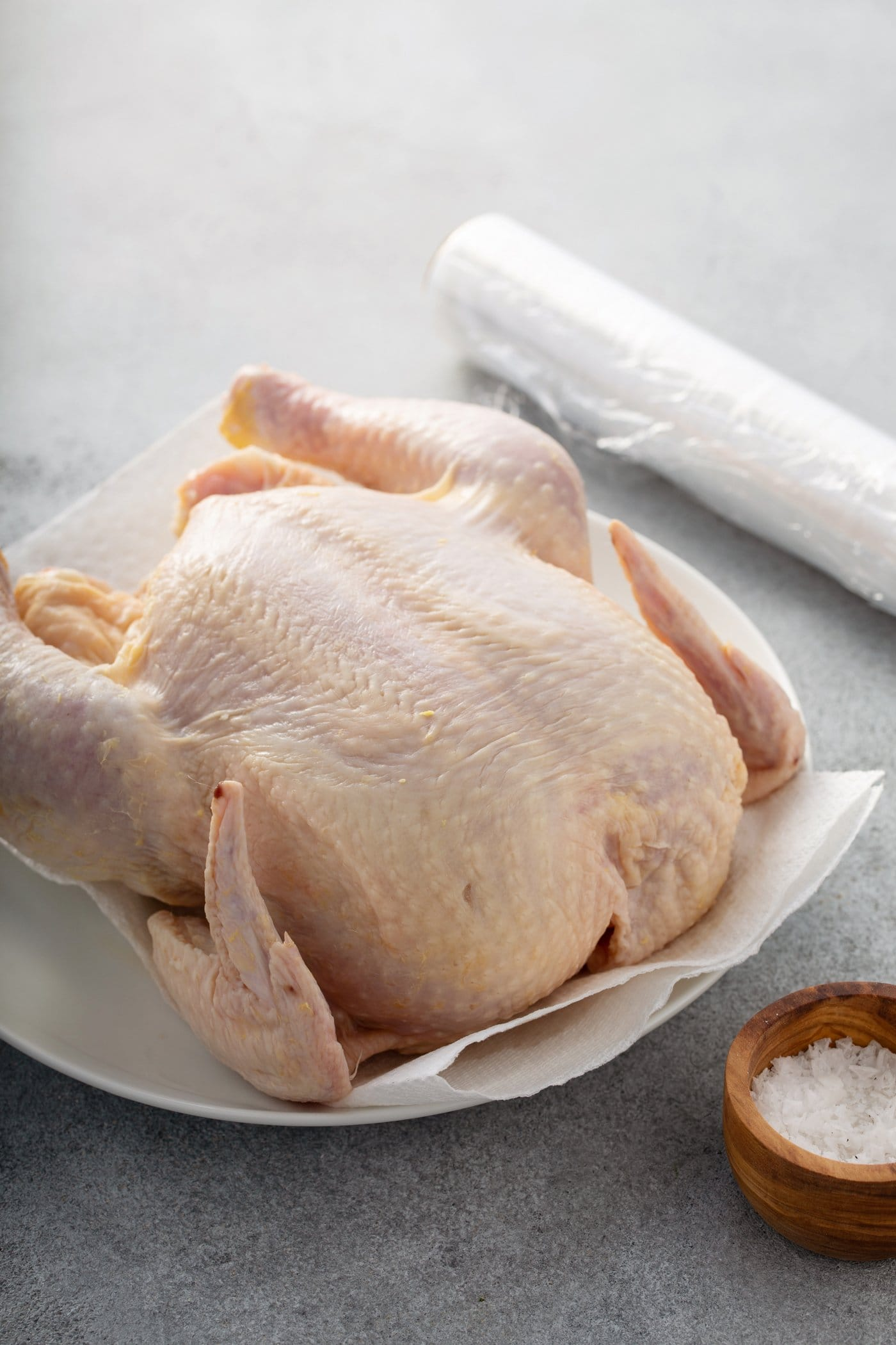 A whole chicken that hasn't been cooked. It is resting on a piece of parchment paper and a roll of parchment paper is next to it. There is a small wooden bowl of salt in front of the chicken.