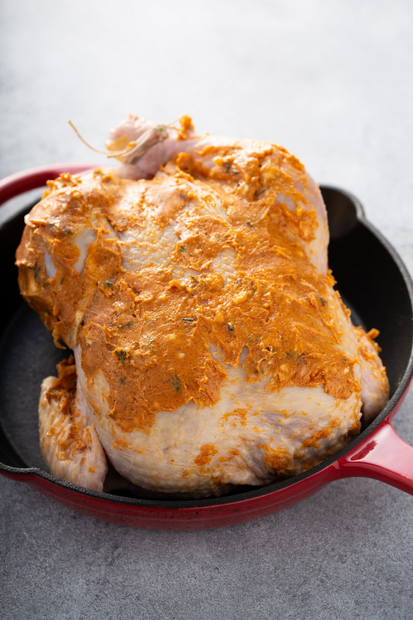 A whole chicken that has been prepped for roasting. You can see the spiced rub that has been rubbed into the chicken. The chicken is in a red Dutch Oven.