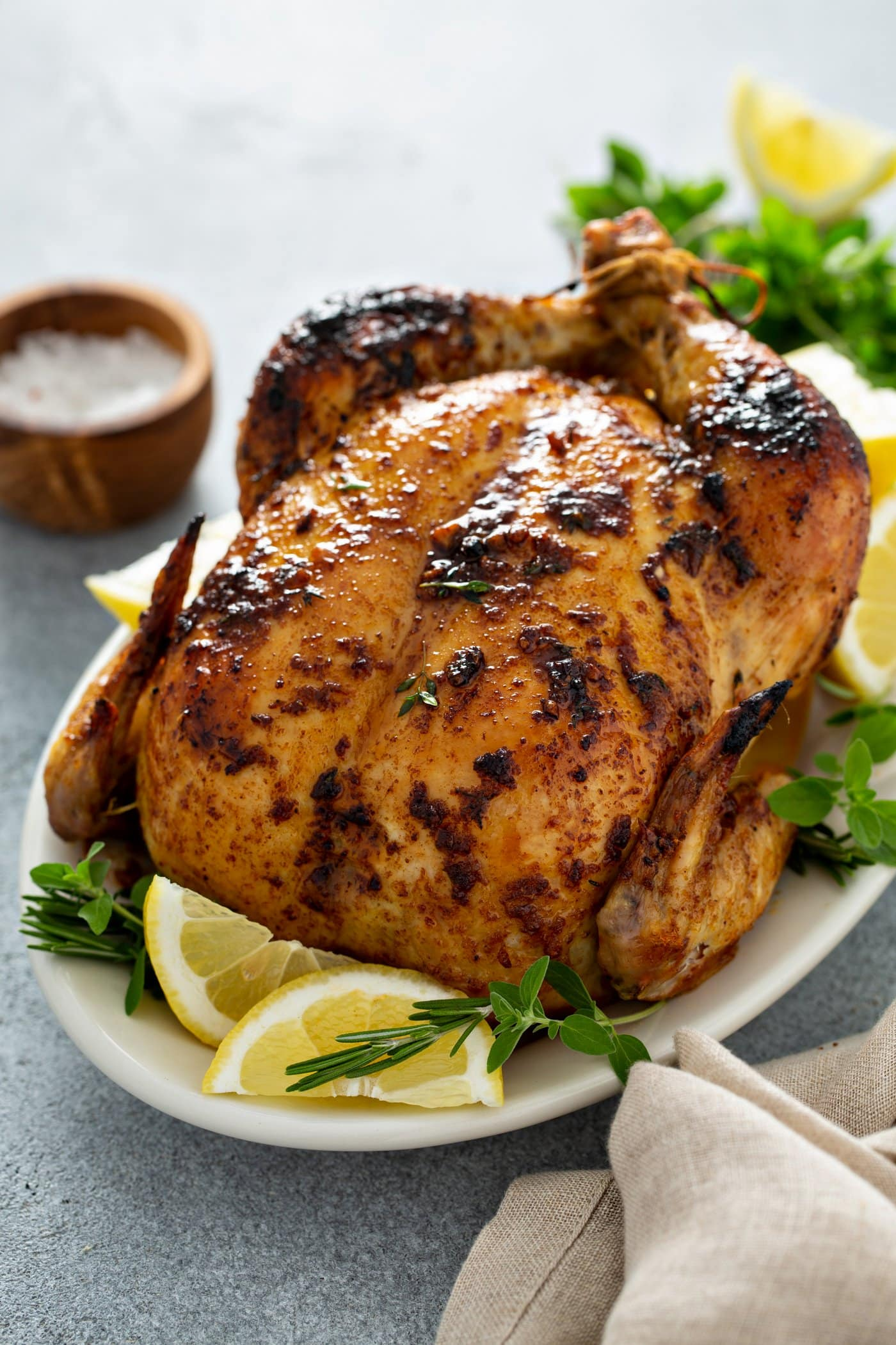 A whole roasted chicken. The chicken is on a platter surrounded by lemon wedges and fresh thyme. A wooden bowl of salt, a linen napkin and a few sprigs of thyme are on the table next to the chicken.