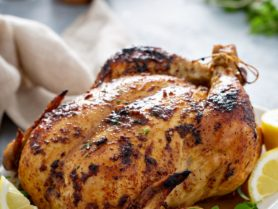 A whole roasted chicken on a white platter with lemon wedges and fresh thyme. There is a linen napkin, salt, pepper and fresh thyme on the table next to the chicken.