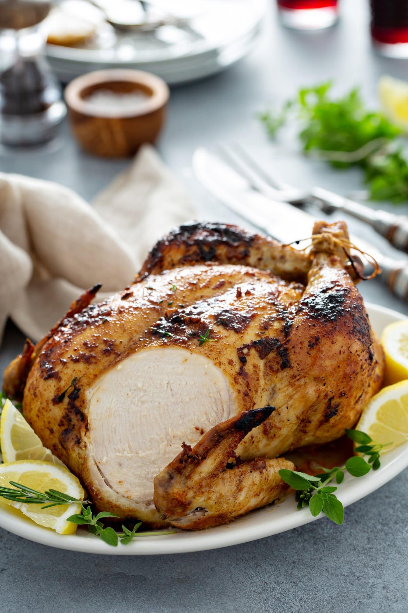 A whole roasted chicken with a slice from the breast. It is sitting on a white platter surrounded by fresh thyme and lemon wedges. There is a knife and fork, a linen napkin, salt, pepper and fresh thyme on the table next to the chicken.