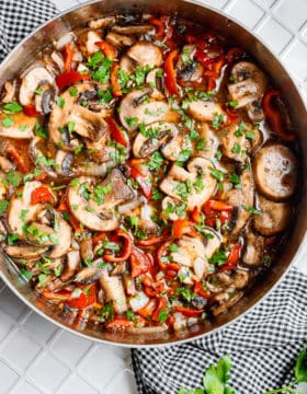 a skillet full of saucy sauteed mushrooms