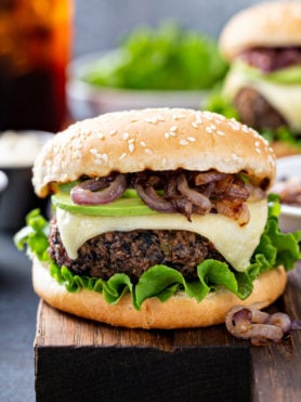 A black bean burger on a sesame seed bun. It is dressed with avocado, onions, cheese and lettuce.