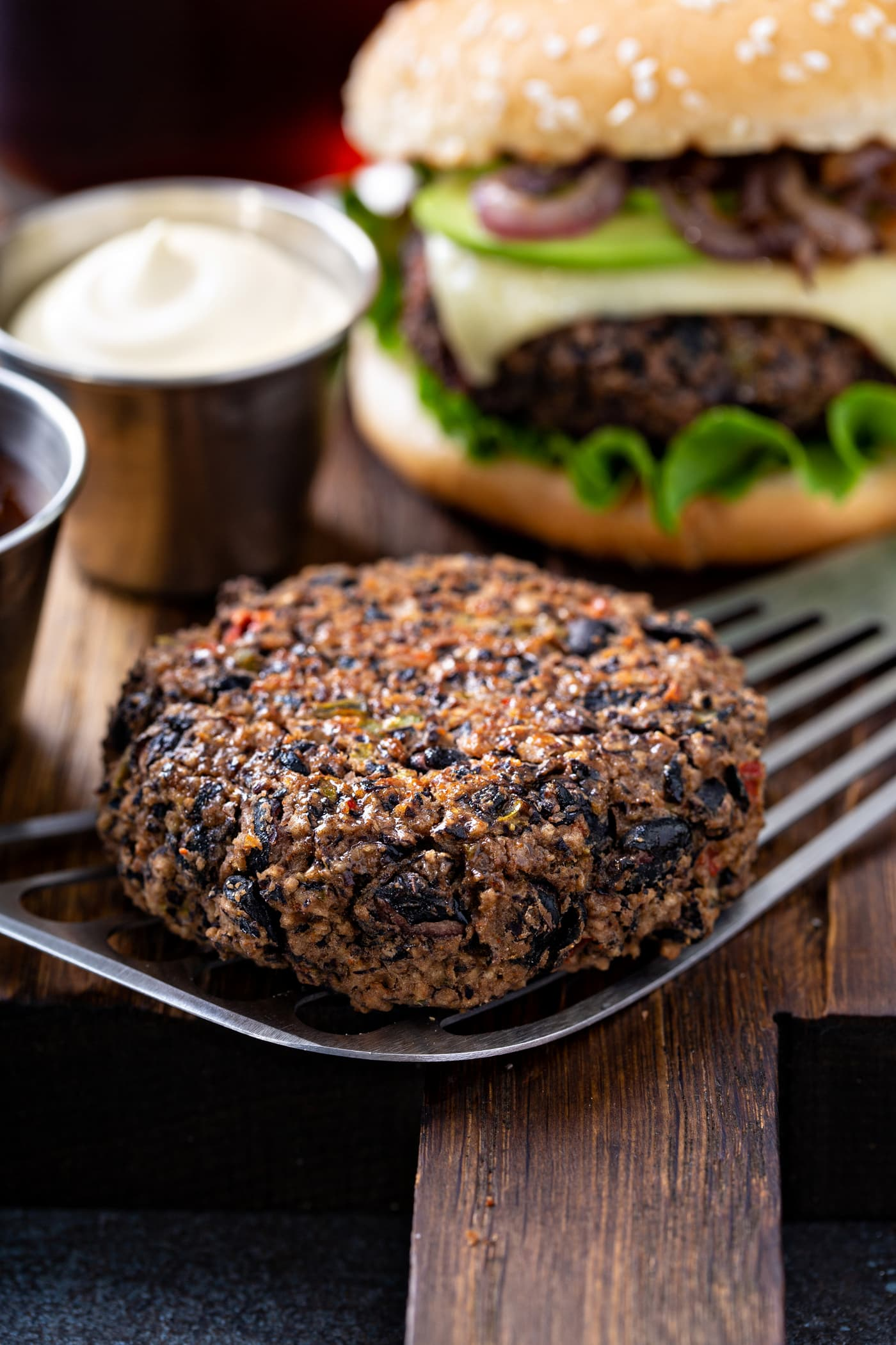 A cooked black bean burger patty on a spatula with a small cup of mayo in the background and a burger on a sesame seed bun dressed with lettuce, cheese, avocado and onions.