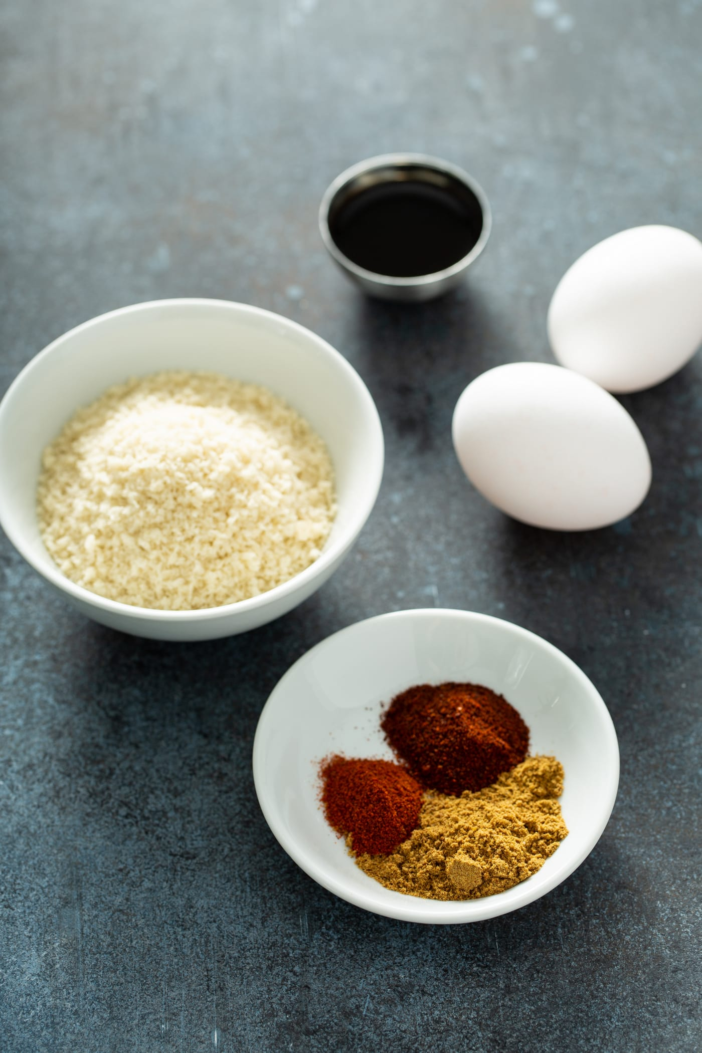 A white bowl with bread crumbs, a white bowl with cumin, paprika and chili powder, two white eggs, and a small container of Worcestershire Sauce.