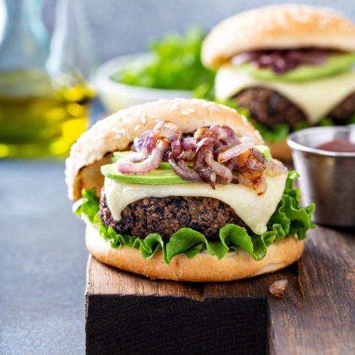 A table top with two black bean burgers on sesame seed buns. The burgers are topped with onions, avocados, cheese and lettuce. There is a bowl of lettuce and a container of oil in the background.