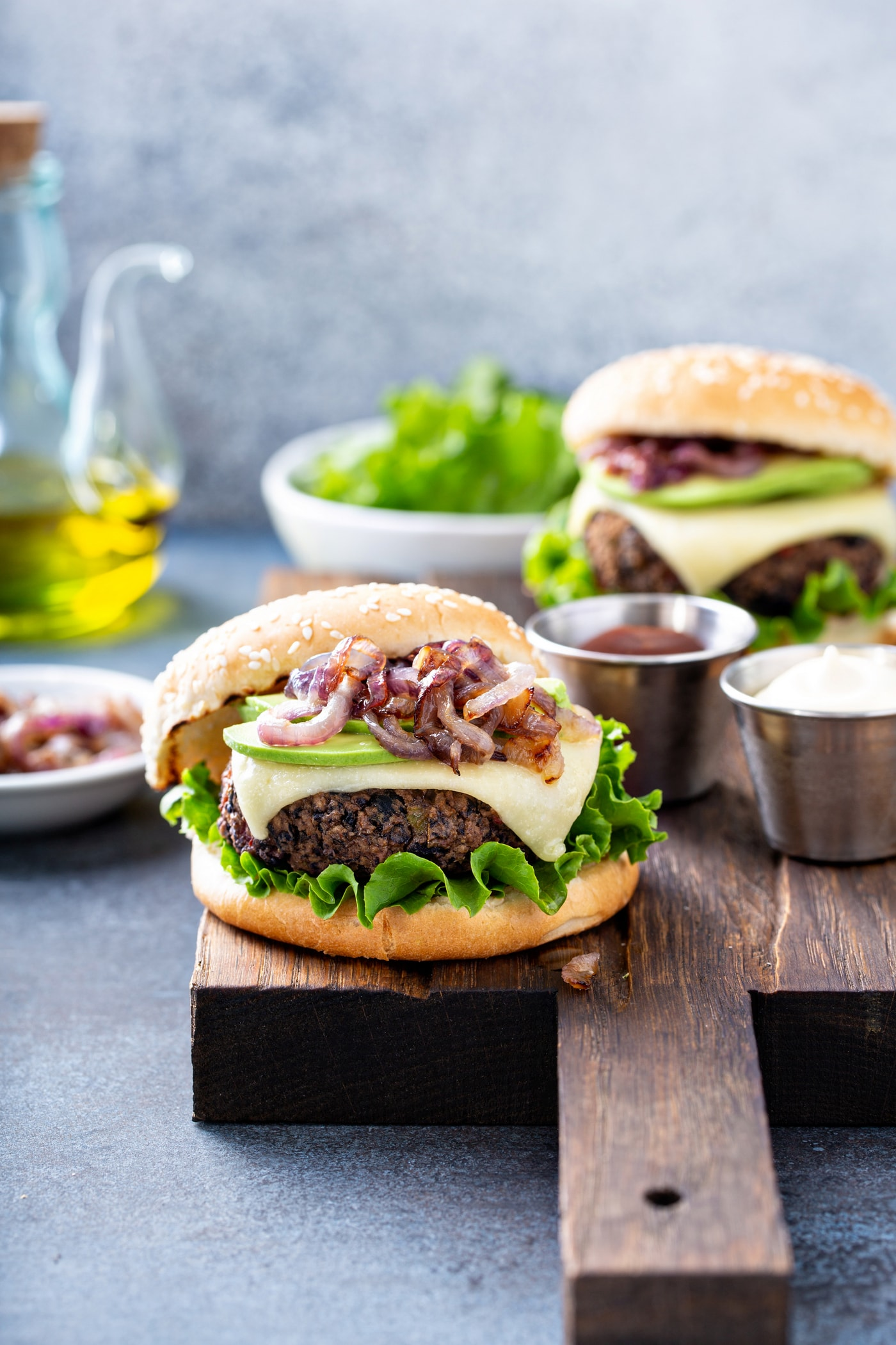 A black bean burger on a sesame seed bun topped with onions, avocado, cheese, and lettuce. There is another burger in the background and a bowl of lettuce, a container of oil, a dish of sliced onions, and a container of mayo.