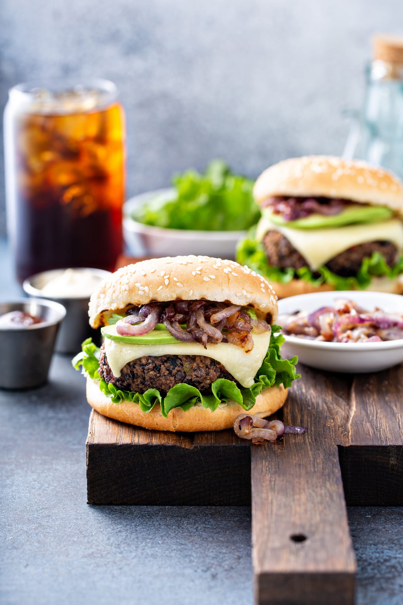A black bean burger on a sesame seed bun topped with onions, avocado, cheese and lettuce. There is another burger, a bowl of lettuce, a container of onions, a container of mayo and a glass of iced soda in the background.