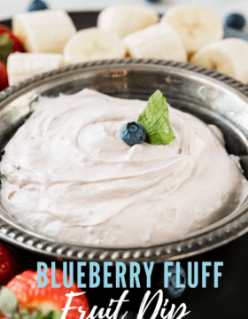 A bowl of blueberry fluff dip with cream cheese and marshmallow fluff with fruit around the bowl