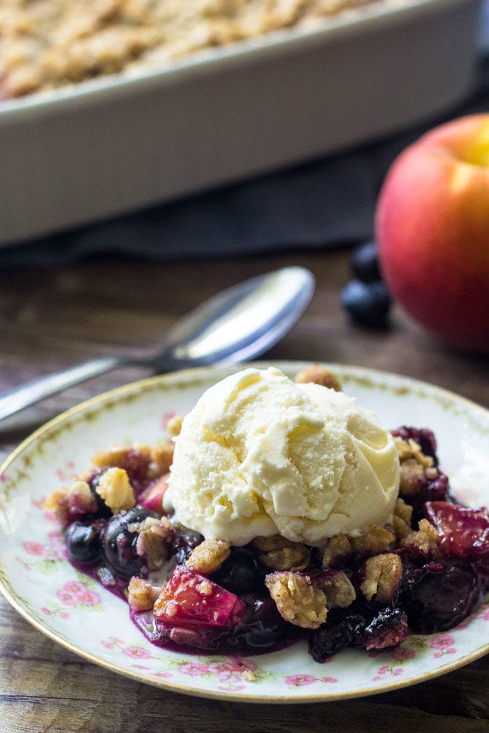 A plate of blueberry peach crumble topped with ice cream.