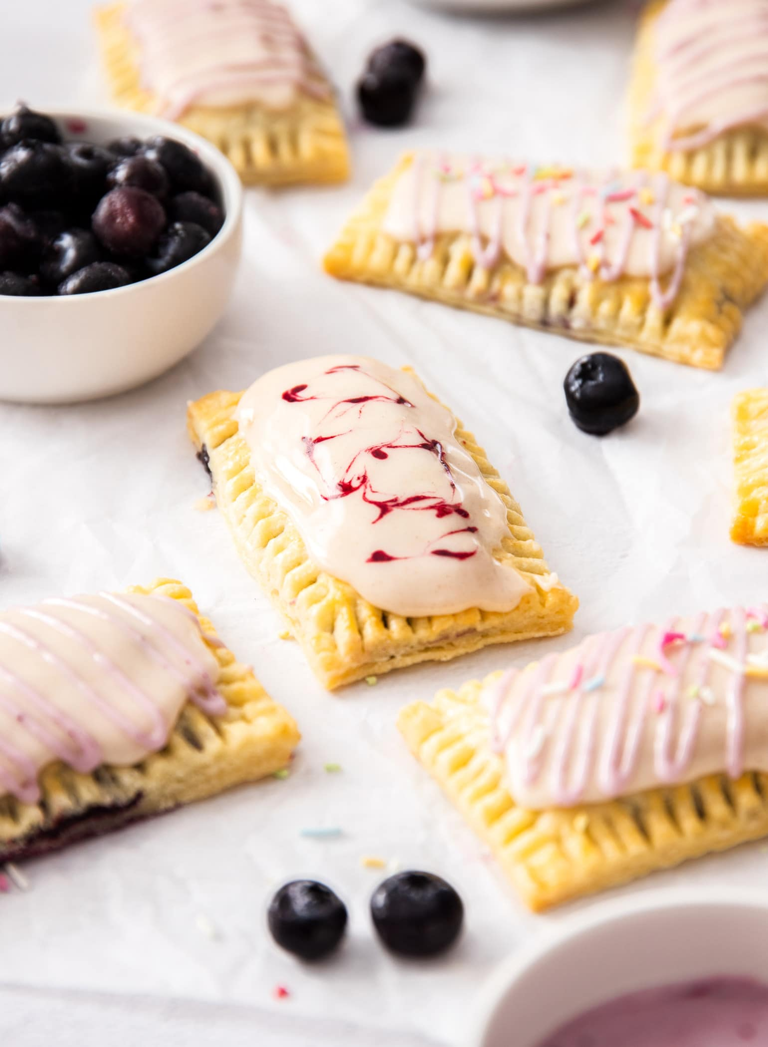 A batch of homemade pop tarts on a sheet of white baking paper. A small white bowl of blueberries.