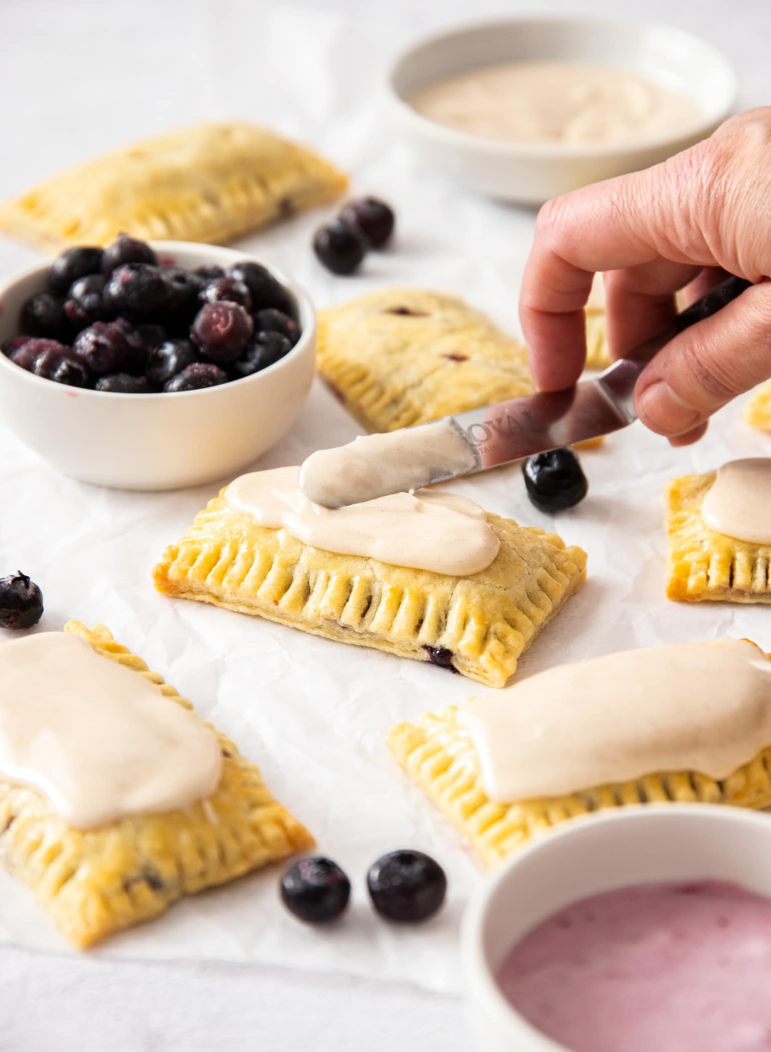 homemade pop tarts being spread with icing. A small white bowl filled with blueberries to the side.