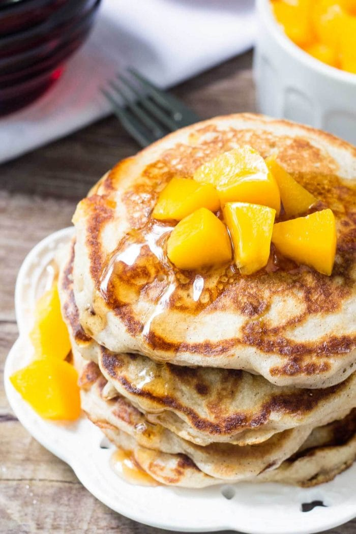 stack of peach pancakes on white plate with diced fresh peaches on top