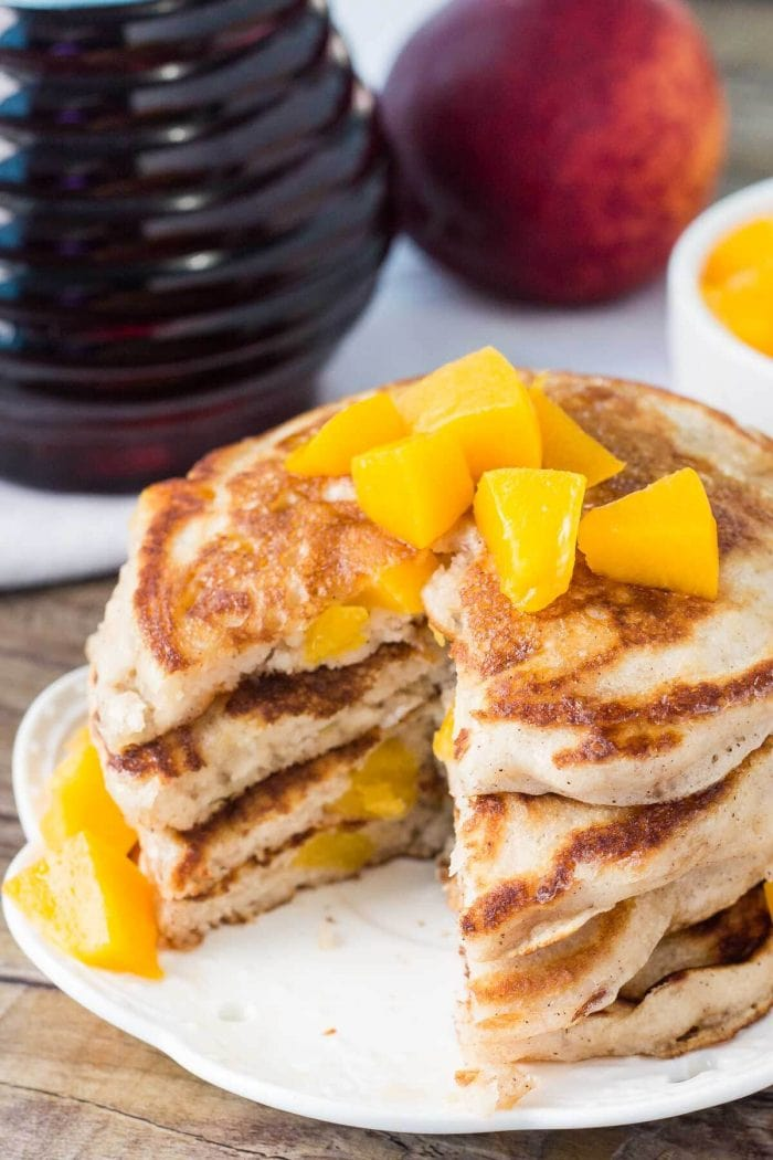 sliced stack of brown sugar cinnamon pancakes with peaches on top