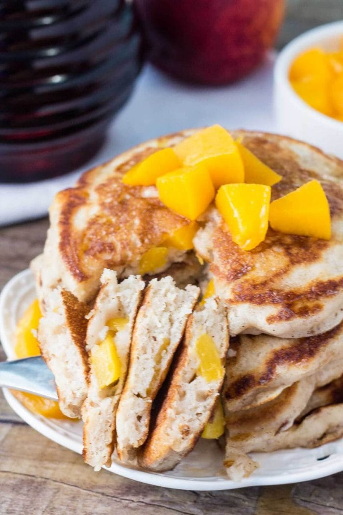 stack of peach pancakes on white plate that have been cut into
