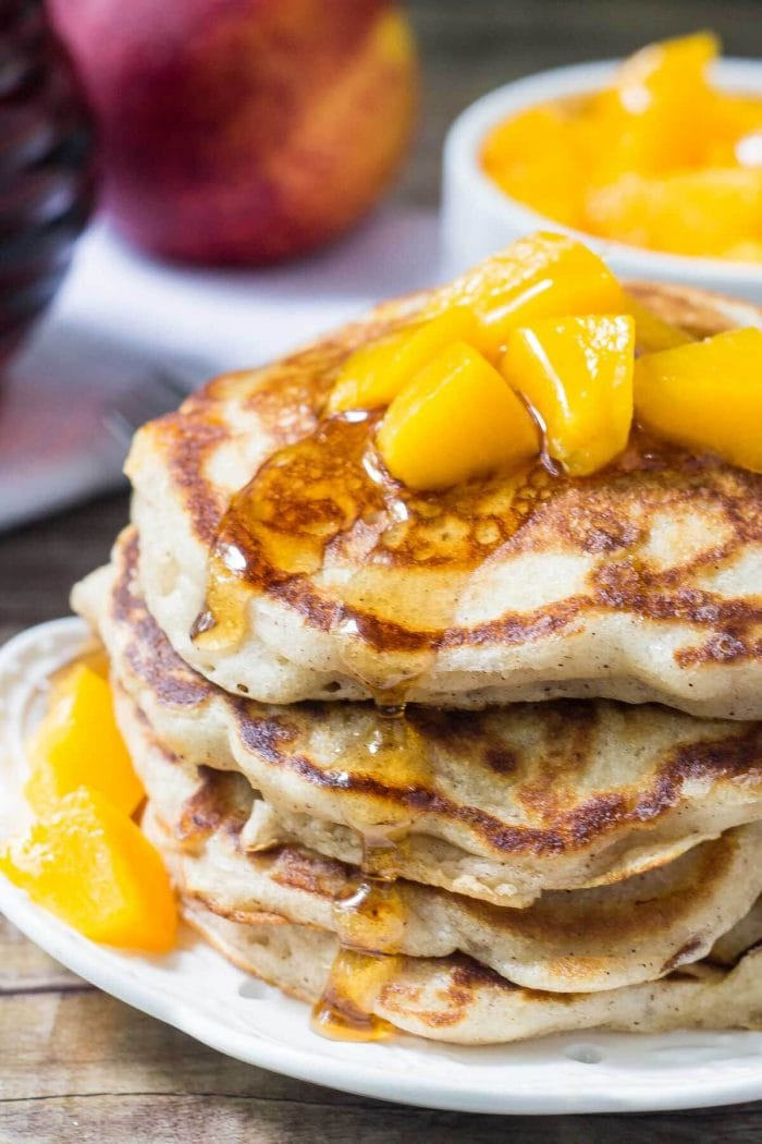 stack of brown sugar cinnamon peach pancakes with peach topping on white plate
