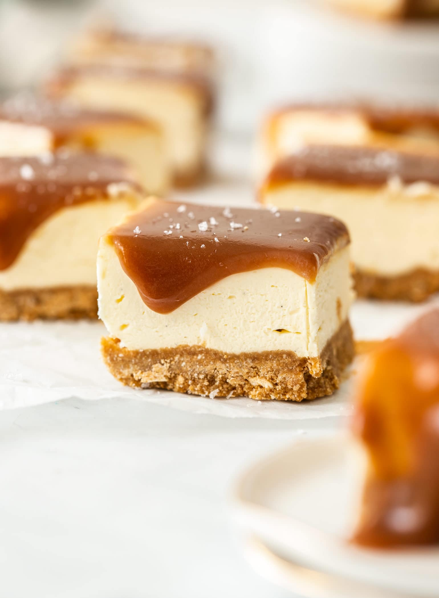 Closeup of a caramel topped cheesecake bar on a piece of white baking paper