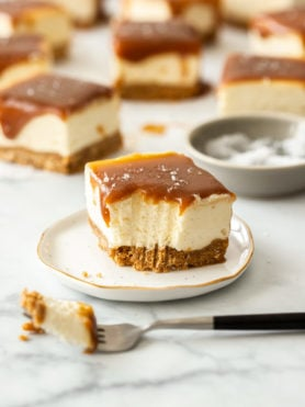 A slice of caramel cheesecake bar on a small white plate with others in the background and a fork in the front
