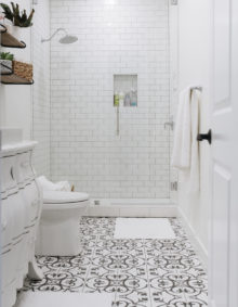 Black and white tile bathroom with a dresser turned into a vanity and a tall infinity glass shower with white subway tile, now that's a guest bathroom I want to visit!