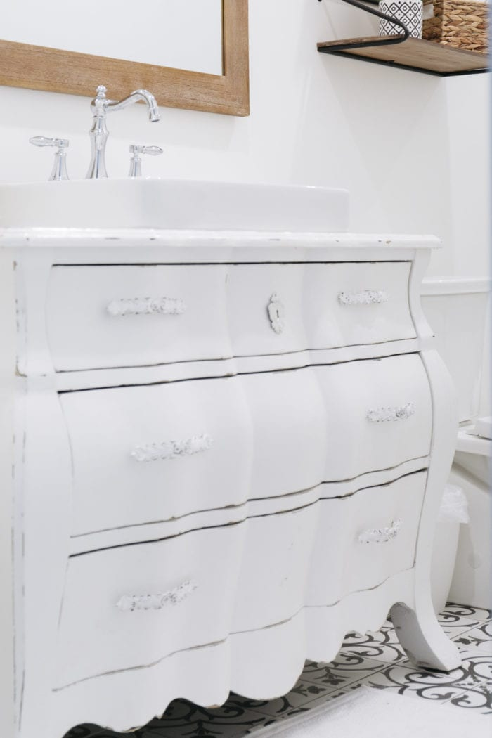 A white dresser gets new life as a bathroom vanity. We cut out the drawers around the plumbing, still leaving pieces with new sides nailed in to hold things.