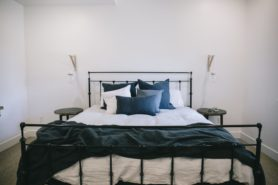 Black iron bed frame with grey bedding