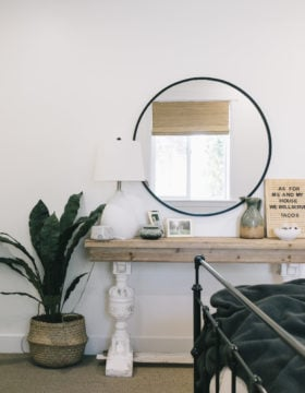 Urban Outfitters Black Round Mirror over a simple side table with a modern floor plant #modern #bedroomUrban Outfitters Black Round Mirror over a simple side table with a modern floor plant
