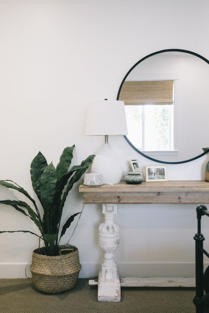 Urban Outfitters Black Round Mirror over a simple side table with a modern floor plant #modern #bedroom