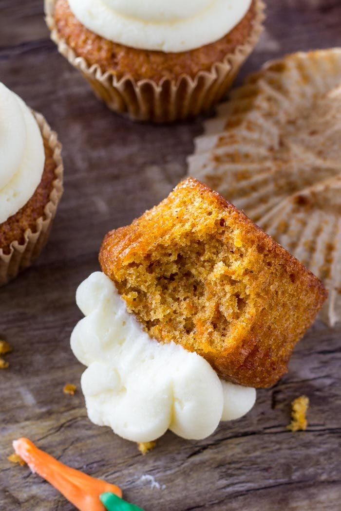 carrot cake cupcake with bite missing laying on its side