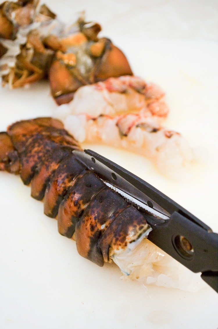 A lobster tails' shell is cut with scissors right down the top center to remove the meat inside for Cheesy Lobster Shrimp and Crab Dip.