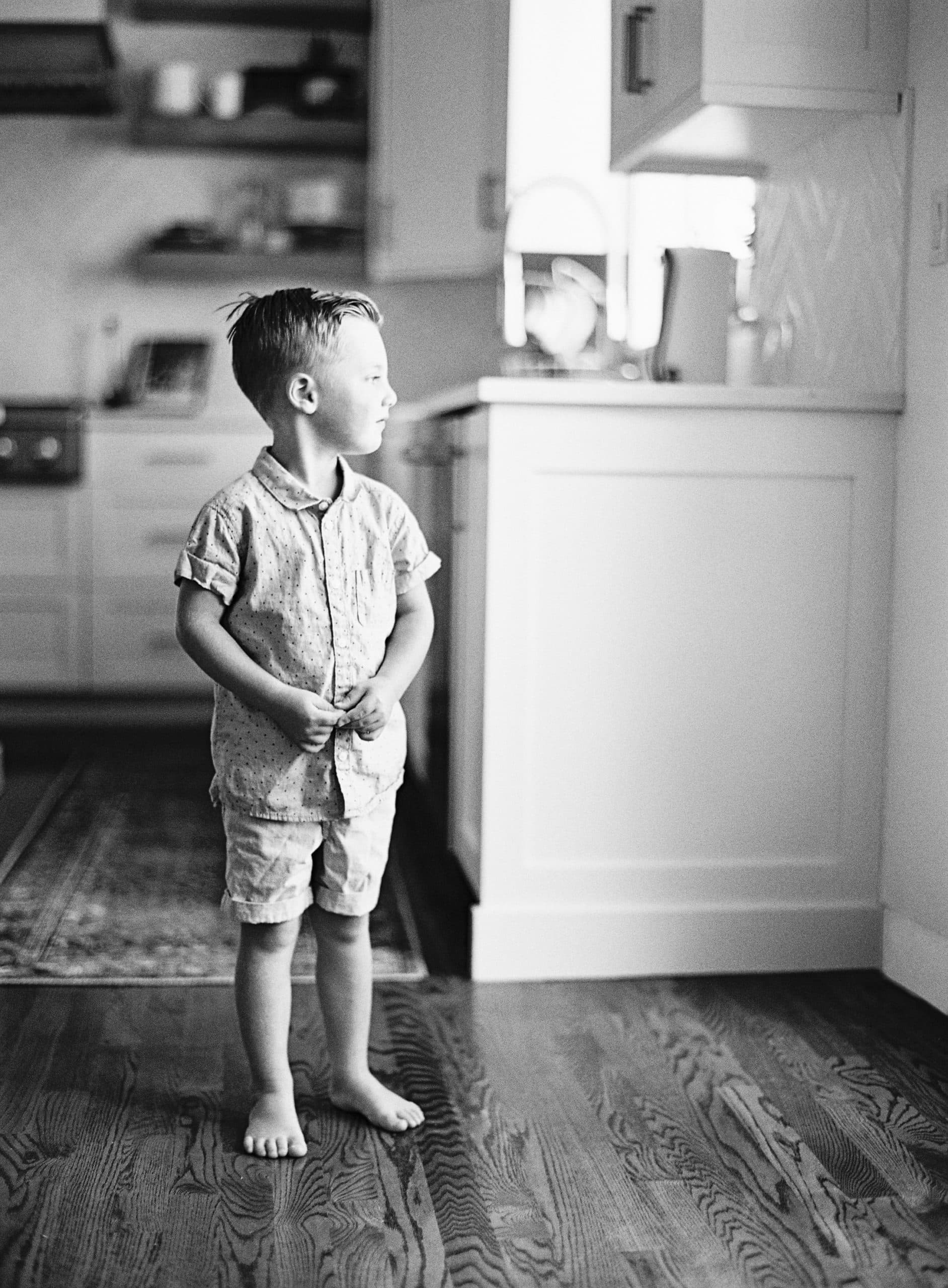 A photo of a young boy staring out the window.