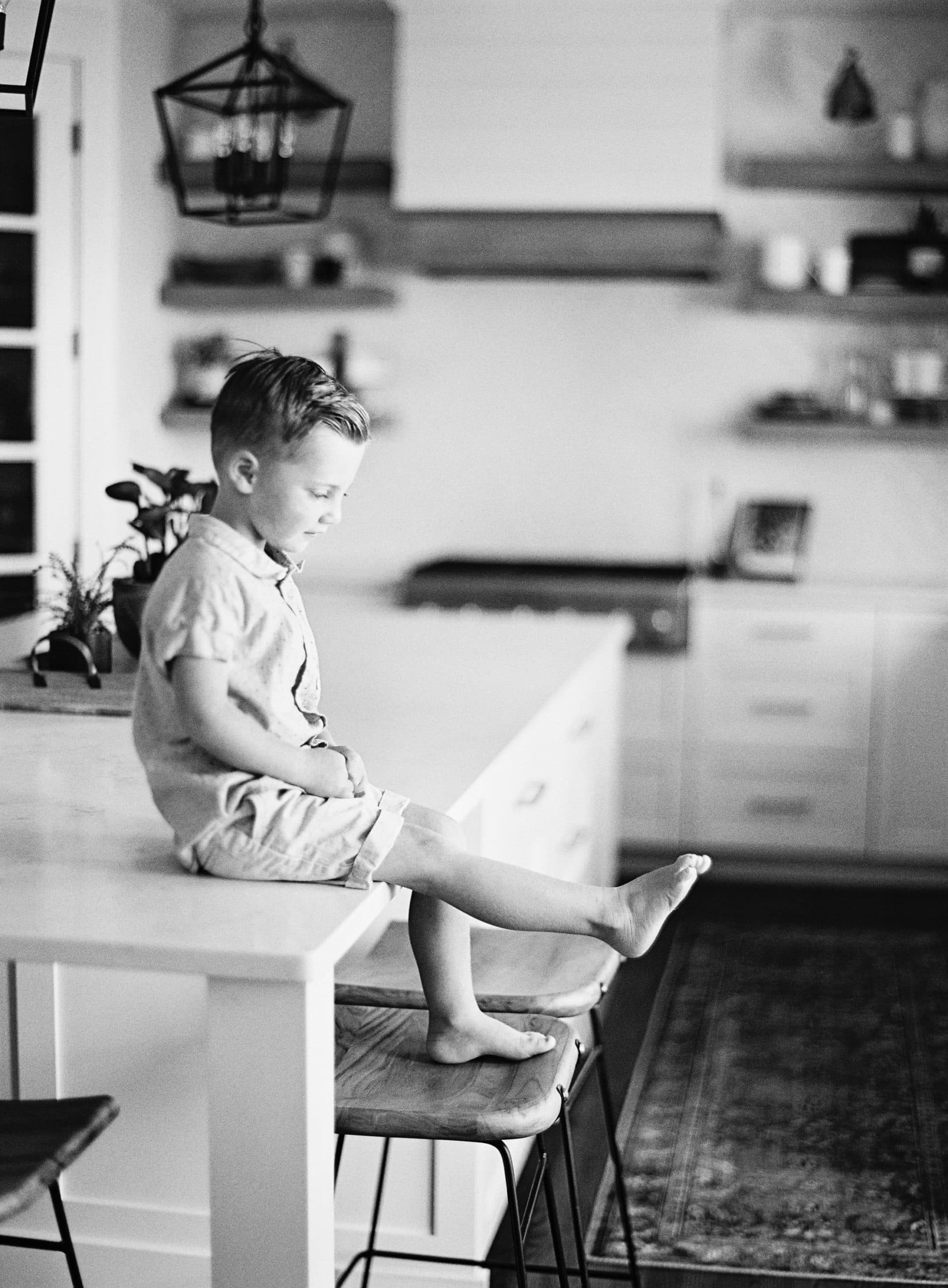 A photo of a young boy sitting on the counter looking at his toes.