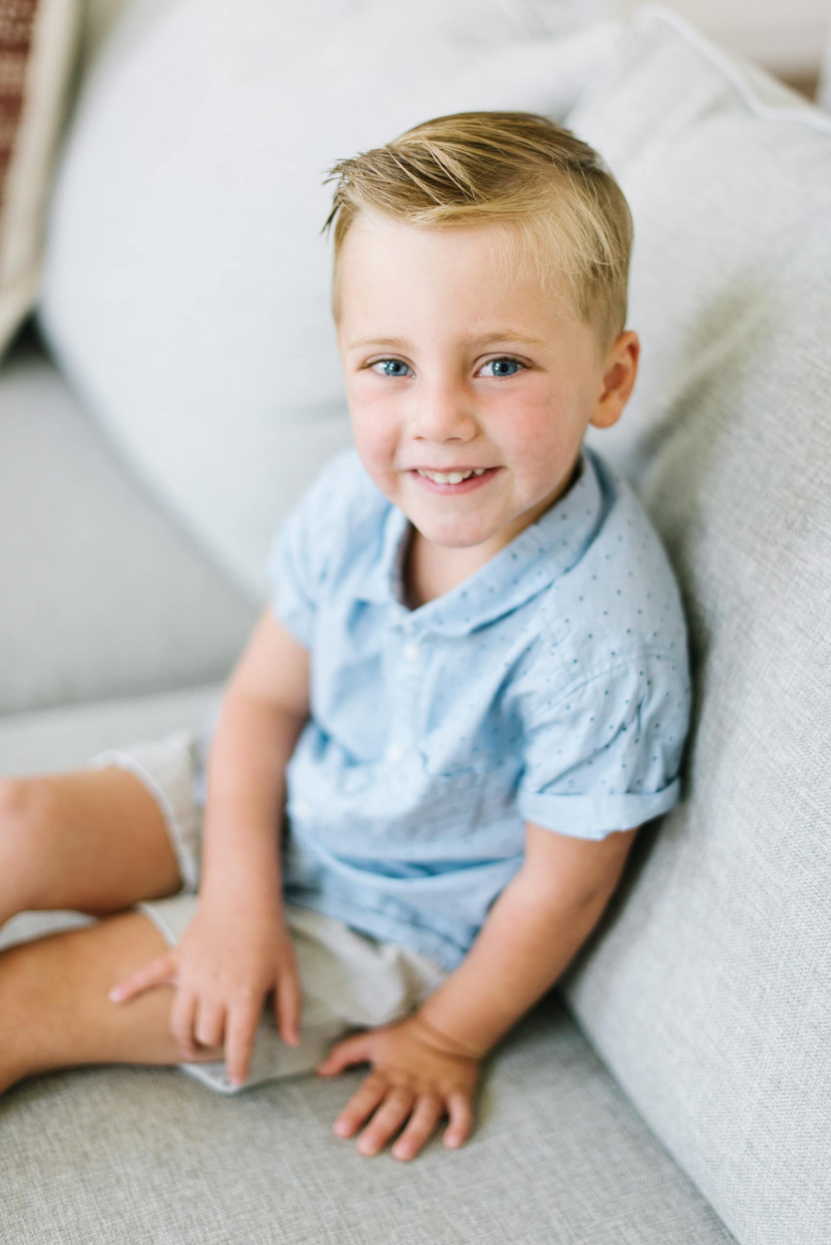 a photo of a young cute boy sitting on a couch