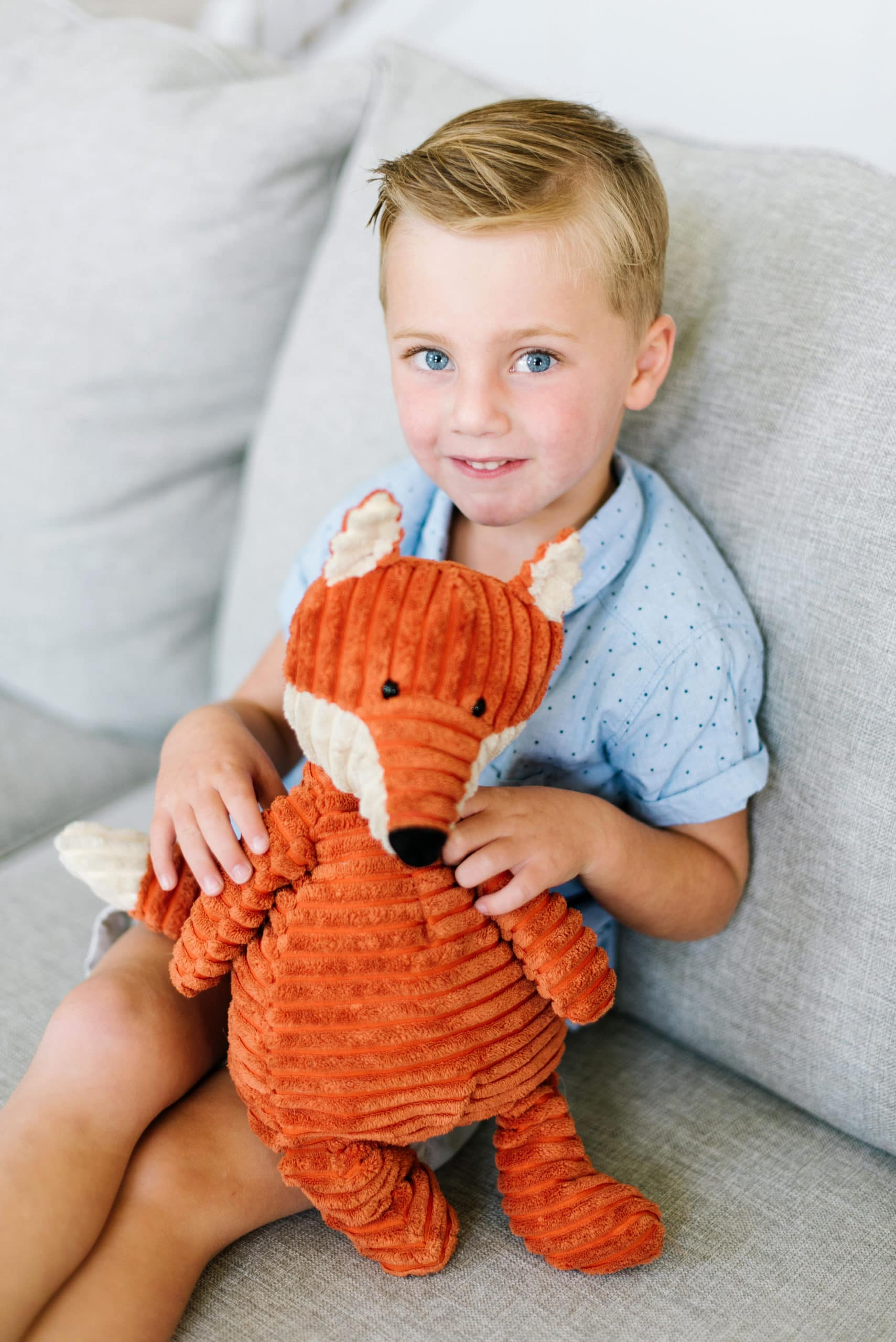 a photo of a young blue eyed boy sitting on a couch with his stuffed toy fox