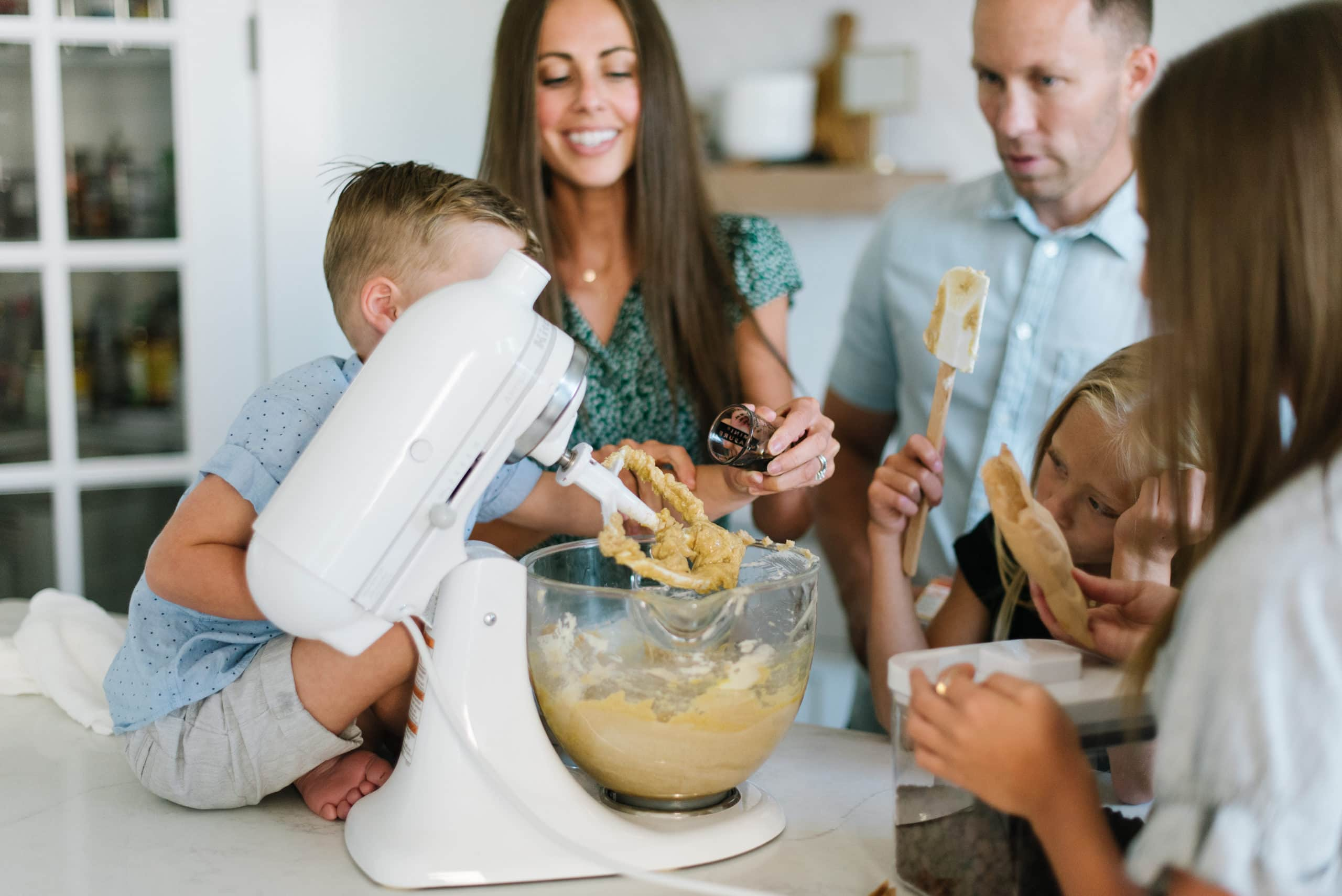 A family standing around a KitchenAid mixer making chocolate chip cookies.
