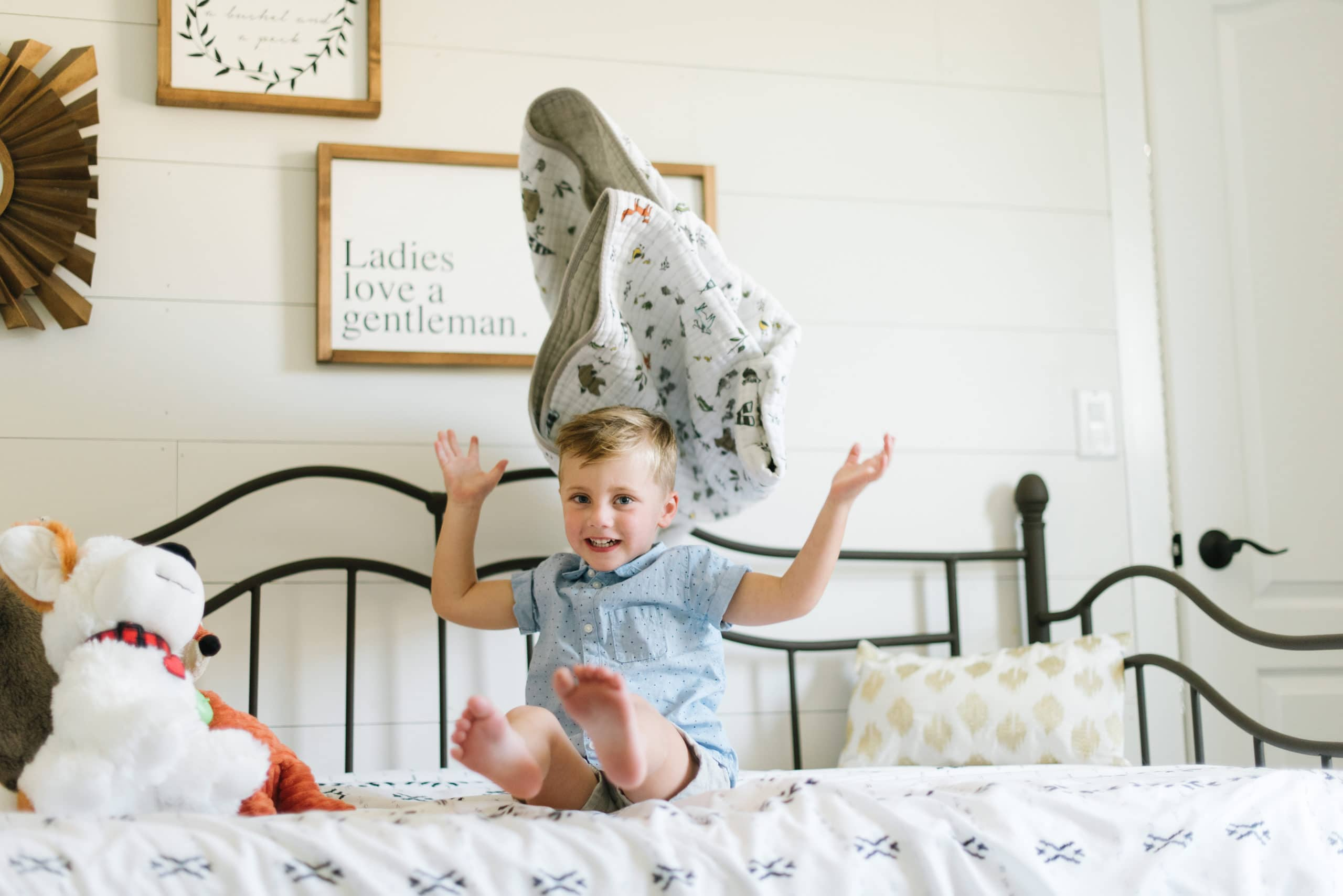 a photo of a young boy sitting on his bef throwing his blanket up in the air