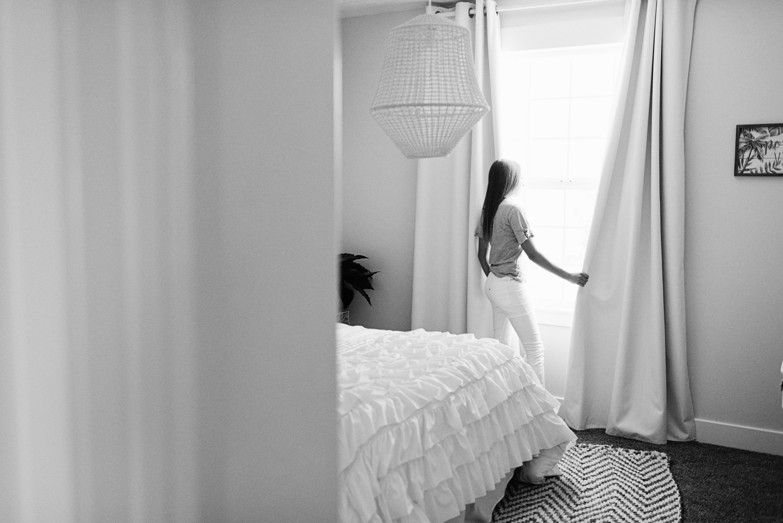 A photo of a young woman looking out a window and holding the curtain.