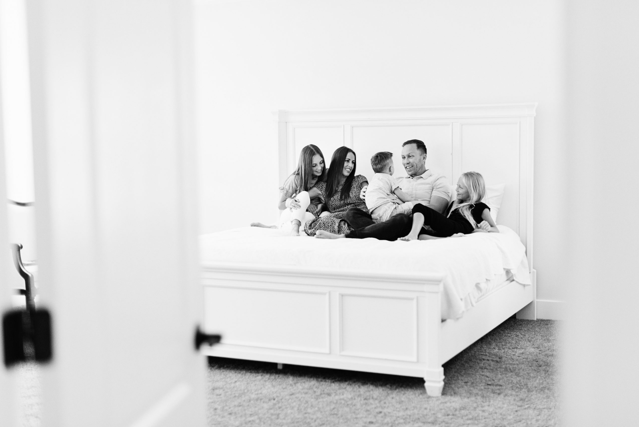 a family sitting on a large white bed enjoying time together