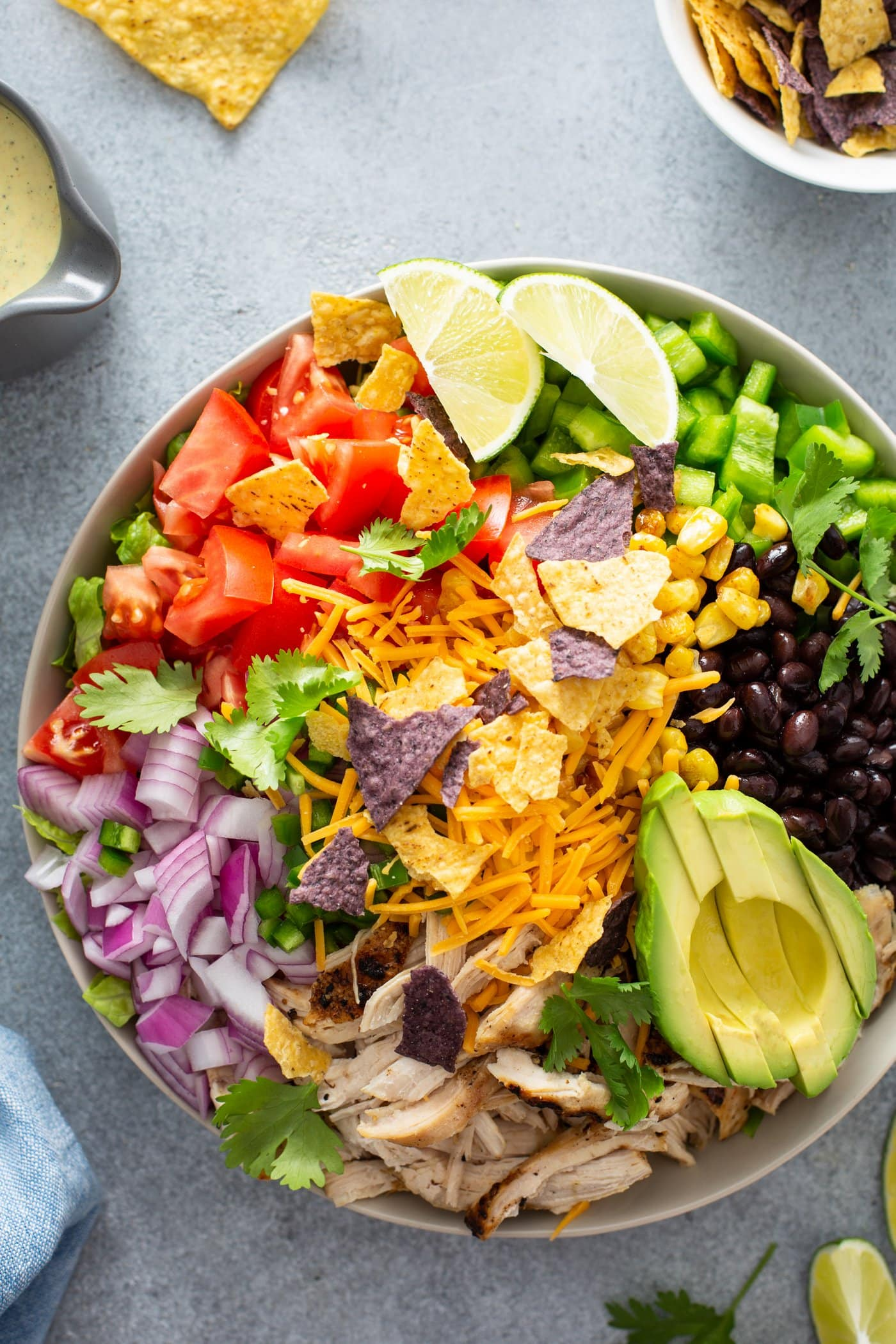 A chicken taco salad in a large bowl. It has chopped tomatoes, red onions, cheese, cilantro, lime wedges, chicken, corn, beans and peppers. There is also a sliced avocado.